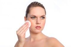 Meisje dat schoonheidsmiddelen katoenen reinigend stootkussen op gezicht gebruikt Royalty-vrije Stock Fotografie