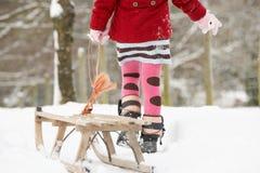 Meisje dat Slee trekt door het Landschap van de Winter royalty-vrije stock afbeeldingen