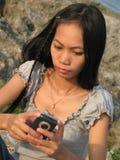 Meisje dat SMS van vakantie verzendt Stock Foto's