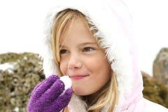 Meisje dat sneeuw eet Stock Afbeeldingen