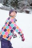Meisje dat sneeuwbal werpt stock foto's