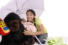 Meisje dat stuk speelgoed in paraplu beschermt Stock Afbeeldingen