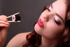 Meisje dat sushi met eet eetstokjes royalty-vrije stock foto's