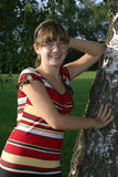 Meisje dat tegen een boom leunt. Stock Afbeeldingen