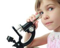 Meisje dat tegen oog aan microscoop wordt geleund Stock Foto's