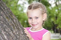 Meisje dat uit door boom piept Royalty-vrije Stock Afbeeldingen