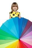 Meisje dat uit van achter de kleurrijke paraplu piept Stock Foto