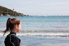Meisje dat in wetsuit uit aan overzees kijkt royalty-vrije stock afbeelding