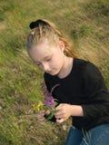 Meisje dat wilde bloemen plukt Stock Foto's