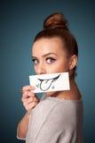 Meisje die witte kaart met glimlach houden die op gradiëntachtergrond trekken royalty-vrije stock foto