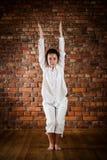 Meisje dat yoga uitoefent tegen bakstenen muur Stock Foto