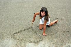Meisje dat in zand hert maakt stock foto