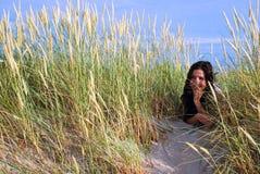 Meisje dat in zandduinen legt Stock Foto's