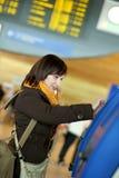 Meisje dat zelf-inschrijving in de luchthaven doet stock afbeeldingen