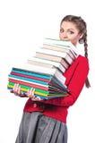 Meisje dat zich met een bos van boeken bevindt stock afbeelding