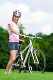 Meisje dat zich met een fiets bevindt Stock Foto's