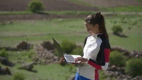 Meisje dat zich met laptop bevindt stock videobeelden