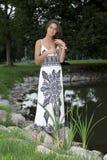 Meisje dat zich op de rand van de vijver bevindt Royalty-vrije Stock Foto