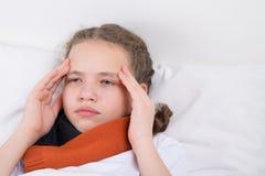Meisje dat ziek is en in een wit die bed ligt, door hoofdpijnen wordt gekweld royalty-vrije stock foto's