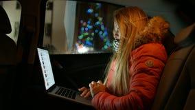Meisje in de auto en de werken bij laptop 4K 30fps ProRes stock videobeelden