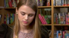 Meisje in de bibliotheek die voor het examen voorbereidingen treffen sluit stock video