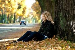 Meisje in de bladeren Stock Afbeelding