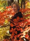 meisje in de bladeren van de dalingsesdoorn Stock Foto