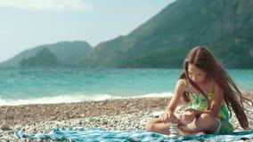 Meisje de bouwtoren van kiezelstenen op zee strand Kalme de kindbouw steentoren stock video