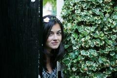 Meisje in de deur van een tuin Stock Afbeeldingen