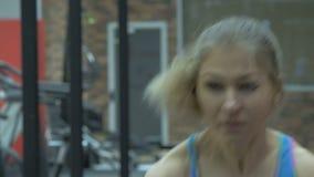 Meisje in de de gymnastiek, gewichten van het liftenmetaal en het fronsen met inspanning stock video