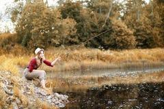 Meisje in de herfst met een hengel Stock Foto's