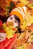 Meisje in de herfst oranje hoed op bladgroep. Stock Foto
