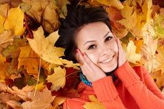 Meisje in de herfst oranje hoed op bladgroep. Stock Afbeeldingen