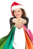 Meisje in de hoed van de Kerstman dragende het winkelen zakken stock fotografie