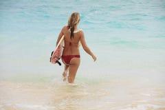 Meisje in de oceaan met haar surfplank Stock Afbeelding