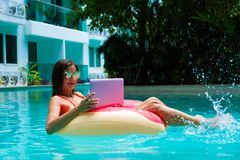 Meisje in de opblaasbare cirkel in de pool met laptop, het concept het freelancing en recreatie stock fotografie