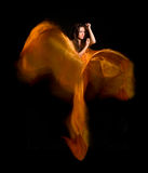 Meisje in de oranje kleding van vliegende stof Stock Foto's