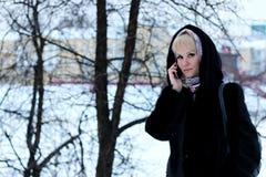 Meisje in de sneeuw van de de besprekingstelefoon van de de Winterstraat Stock Foto
