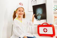 Meisje in de speeltandarts van het artsenkostuum met röntgenstraal stock afbeeldingen