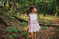 Meisje de status in het hout die een stuk speelgoed houden draagt ter beschikking Royalty-vrije Stock Afbeeldingen