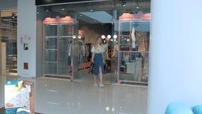 Meisje in de toonzaal van de kledingsopslag stock videobeelden
