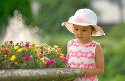 Meisje in de tuin het bewonderen bloemen stock fotografie