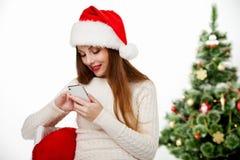 Meisje in de vraagtelefoon van de santahoed door Kerstmisboom Stock Foto