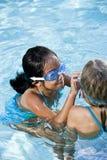 Meisje in de vriend van de zwembadhulp met beschermende brillen royalty-vrije stock foto