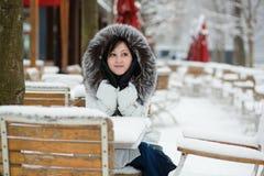 Meisje in de zitting van de bontkap in een openluchtkoffie op een winte Royalty-vrije Stock Fotografie