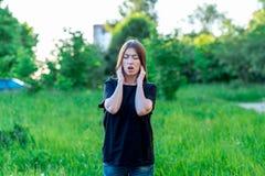 Meisje in de zomer in een park in aard Houdt emotioneel zijn oren van luid geluid Drukte haar open ogen emotioneel royalty-vrije stock foto's