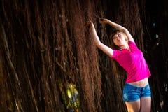 Meisje in denimborrels die met bruine tropische wijnstokken stellen royalty-vrije stock foto