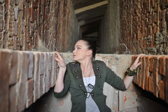 Meisje dichtbij de bakstenen muur in militaire stijl stock foto