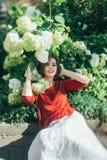 Meisje dichtbij de bloemen van hydrangea hortensia Stock Foto