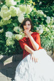 Meisje dichtbij de bloemen van hydrangea hortensia Stock Fotografie